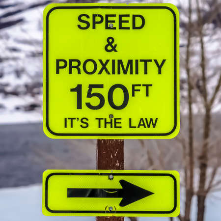 Square Speed and Proximity road sign against a snow covered mountain in winter Reklamní fotografie