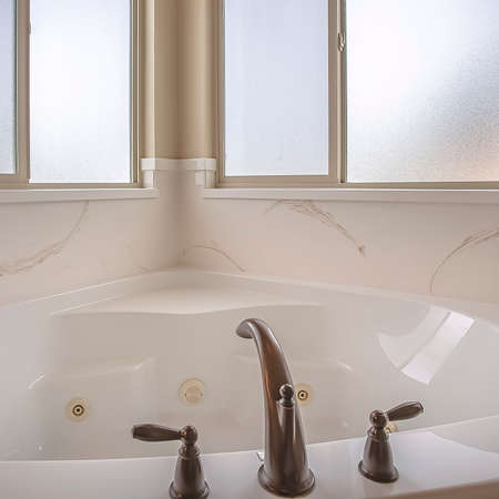 Square Bathroom interior of a home with polished bathtub and frosted windows