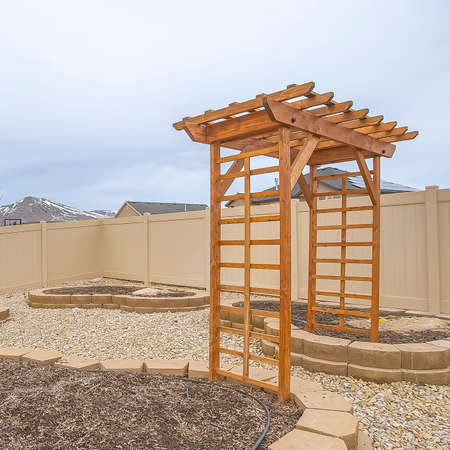 Square Heart shaped planting beds and wooden arbor at the yard of a home