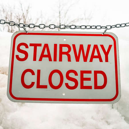 Square Close up of sign that reads Stairway Closed against snow covered slope in winter Standard-Bild - 128118894