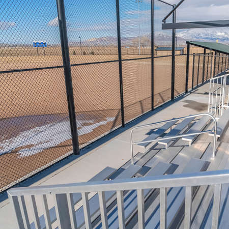 Square frame Bleachers behind the fence of a baseball field with melting snow on the ground