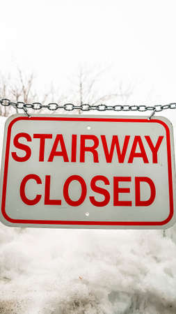Vertical Close up of sign that reads Stairway Closed against snow covered slope in winter Standard-Bild - 128112962