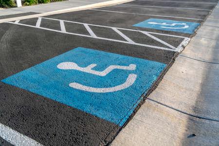 Cerca de una persona en un icono de silla de ruedas pintado sobre el pavimento negro Foto de archivo