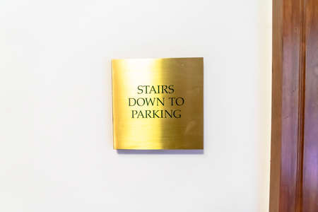 Gold plated sign that reads Stairs Down To Parking against white interior wall