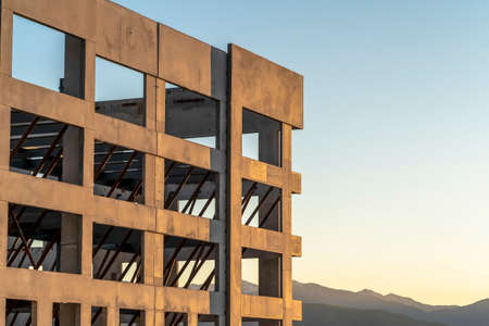 Close up of an unfinished building exterior with mountain and sky background