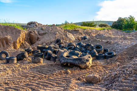 Old black rubber tires discarded on the dry ground with tire tracks Reklamní fotografie