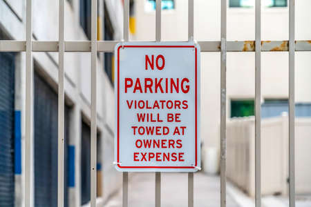 Close up of No Parking sign on awhite metal gate with building in the background Stock Photo