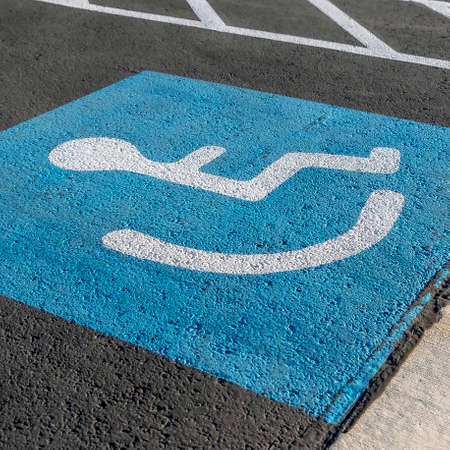 Square frame Close up of a person on a wheelchair icon painted on the black pavement