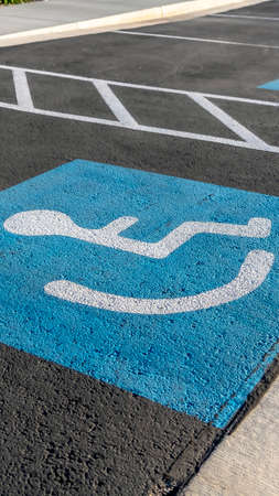 Vertical frame Close up of a person on a wheelchair icon painted on the black pavement