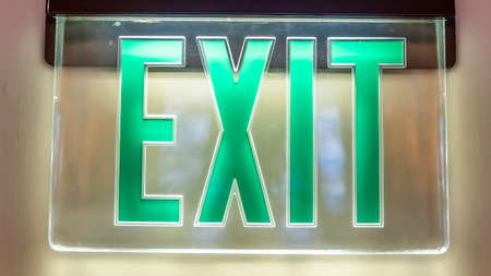 Panorama frame Building interior with a neon green light Exit sign pounted on the white wall