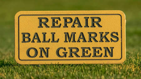 Panorama frame Close up of a sign at a golf course reading Repair Ball Marks On Green