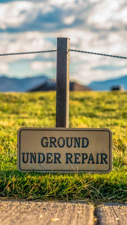 Vertical frame Close up of a Ground Under Repair sign on a grassy terrain along a paved road