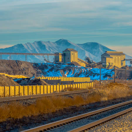 Square Railway track passing in front of a mining area viewed on a sunny day