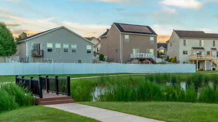 Panorama Neighborhood park with pond bridge pathway bench and trees in front of homes Stock Photo