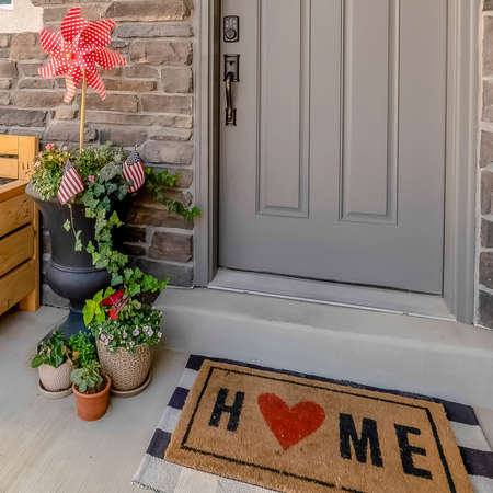 Square frame Porch of a home decorated with wooden chair potted plants wreath and doormat Banco de Imagens