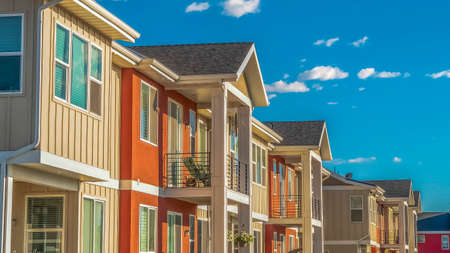 Panorama Homes with white and orange exterior wall against cloudy blue sky on a sunny day