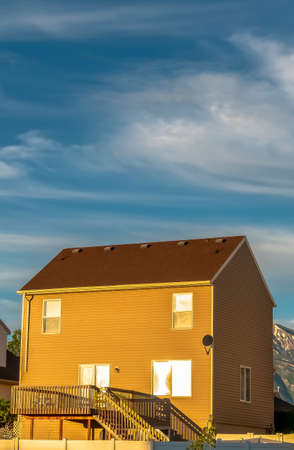 Vertical frame Homes with horizontal wall siding against mountain and cloudy sky on a sunny day Banco de Imagens