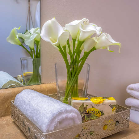 Square frame Tray with towel flowers and soap placed on top of the bathroom vanity counter Banco de Imagens