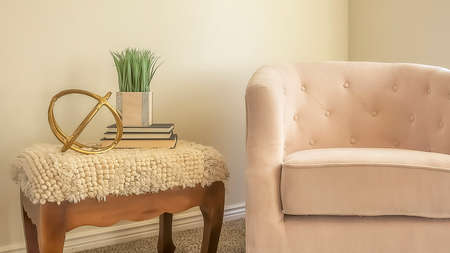 Panorama frame Cozy chair and wooden side table inside a room with white wall and carpet floor