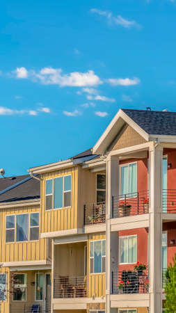 Vertical frame Lovely townhomes viewed against blue sky background on a sunny day