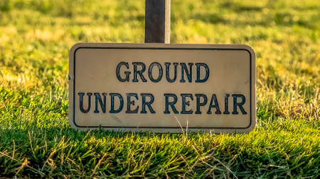 Panorama Close up of a Ground Under Repair sign on a grassy terrain along a paved road