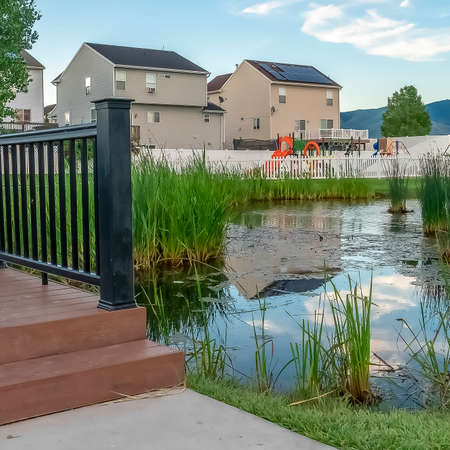 Square Bridge over a pond on a neighborhood park with homes and mountain background