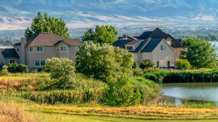Panorama frame Scenic residential area near a lake and surrounded with lush grasses and trees