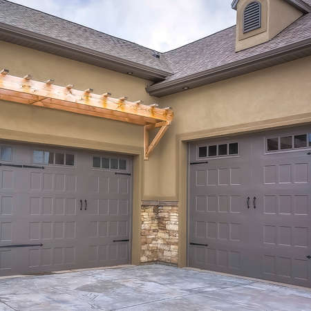 Square Exterior of a home with view of gray double garage doors and stone wall