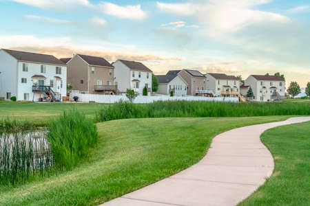Paved walkway on a grassy terrain with houses and cloudy sky in the background