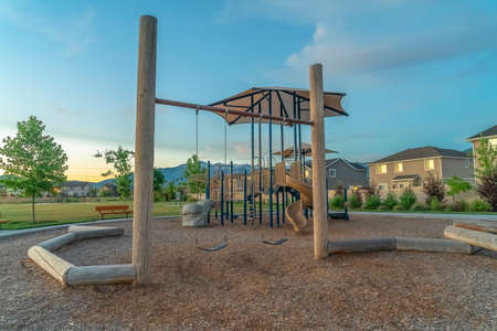 Playground and homes on a neighborhood with view of mountain and cloudy blue sky