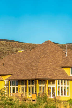 Home exterior with yellow wall and brown roof against mountain and clear sky