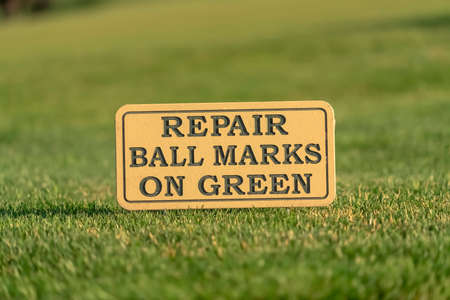 Close up of a sign at a golf course reading Repair Ball Marks On Green Stok Fotoğraf