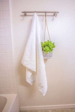 White towel and ornamental plant hanging on a wall rod inside a bathroom