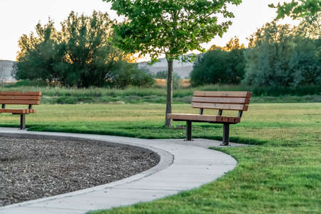 Bench and circular pathway on a grass covered terrain gainst trees and mountain