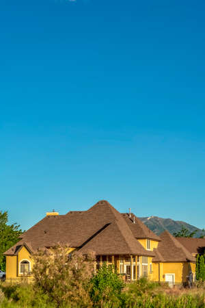 Home with brown roof and yellow wall against mountain and clear blue sky