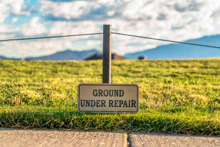 Close up of a Ground Under Repair sign on a grassy terrain along a paved road