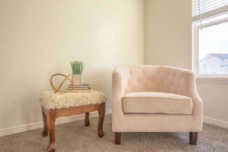Cozy chair and wooden side table inside a room with white wall and carpet floor Banco de Imagens
