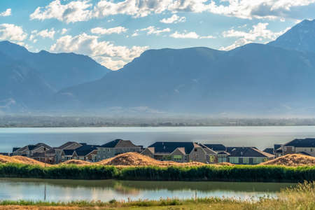 Homes amid a shiny lake with view of distant mountain towering over the valley Banco de Imagens