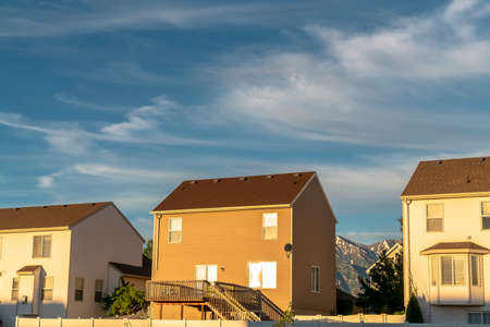 Homes with horizontal wall siding against mountain and cloudy sky on a sunny day