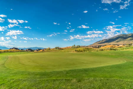Golf course with vivid green fairway under blue sky and clouds on a sunny day