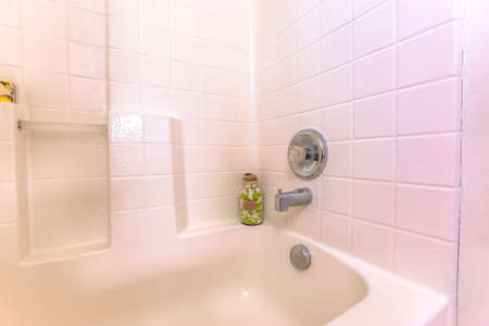 Bathroom interior with close up view of the bathtub and white tiled wall. An ornamental bottle is placed at the corner of the tub and wall.