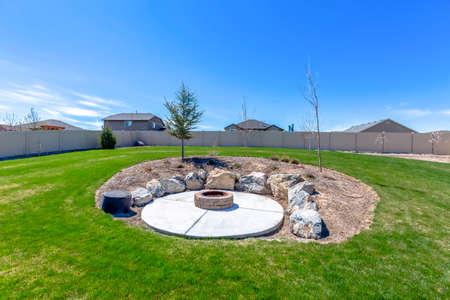 Foyer circulaire entouré de rochers au milieu de la cour herbeuse d'une maison. Une clôture, des maisons et un ciel bleu peuvent être vus en arrière-plan. Banque d'images