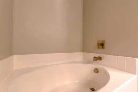 CLose up view of the built in oval bathrtub of a new home with gold faucet. White tiles and gray wall can be seen inside this room.