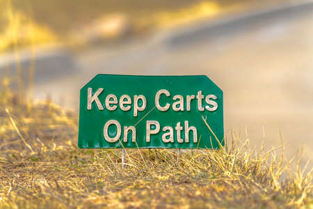 Close up view of a green and white sign that reads Keep Carts On Path Stock fotó