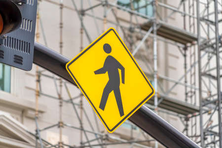 Close up view of a yellow and black diamond shaped Pedestrian Crossing sign Фото со стока