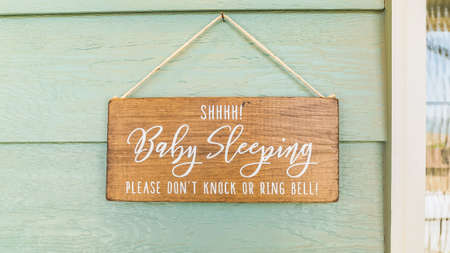 Panorama frame Baby Sleeping sign hanging on the green wall and above the doorbell of a home. Sidelight and door can also be seen in this picture. Standard-Bild - 129446054