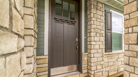 Panorama frame Home entrance with a glass paned brown wooden door and stone brick wall. The front window has a brown wooden shutter and white interior blinds. Standard-Bild - 129446065