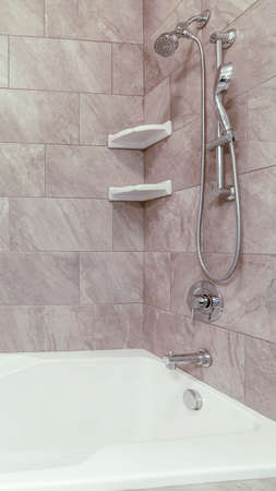 Vertical Square bathtub and stainless steel shower against gray and white tile wall. Soap racks are mounted at the corners of the bathroom wall.