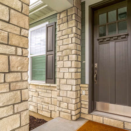 Square frame Home entrance with a glass paned brown wooden door and stone brick wall. The front window has a brown wooden shutter and white interior blinds. Standard-Bild - 129446087