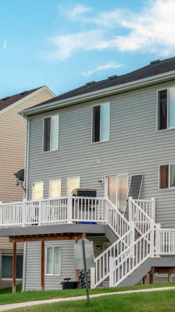 frame A house with gray horizontal wood siding and stairs that leads to the balcony. The house alos has sliding windows and door and dark roof.